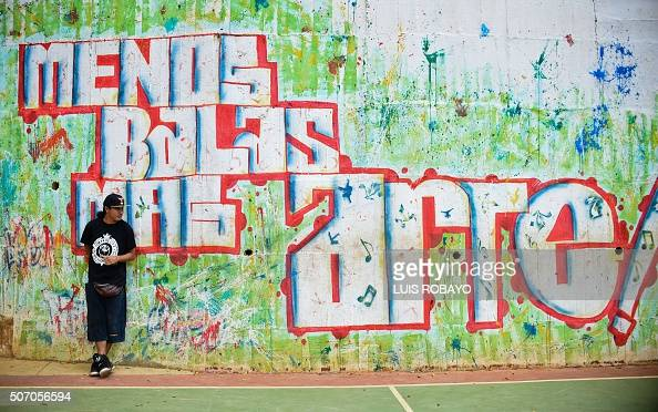 A man leans against a wall with graffiti reading 'Fewer bullets more art' in the Siloe neighbourhood in Cali Colombia on January 9 2016 Considered...