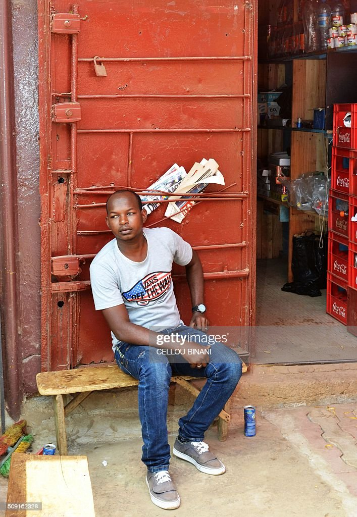 A man leans against an empty newspaper stand in Conakry on February 9, 2016, on a 'press-free day' in honour of a journalist who was shot dead last week. Five media associations called for justice and a 'press-free day' on February 9 in honour of journalist El Hadj Mohamed Diallo who died on February 5 after receiving a bullet to the chest in the capital Conakry during clashes outside the offices of an opposition party. / AFP / CELLOU BINANI