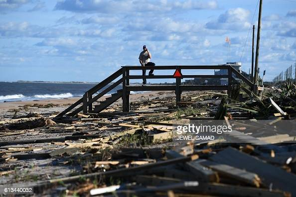 A man leans on a damaged boardwalk at a debris covered beach in St Augustine Florida on October 8 after Hurricane Matthew passed the area Hurricane...