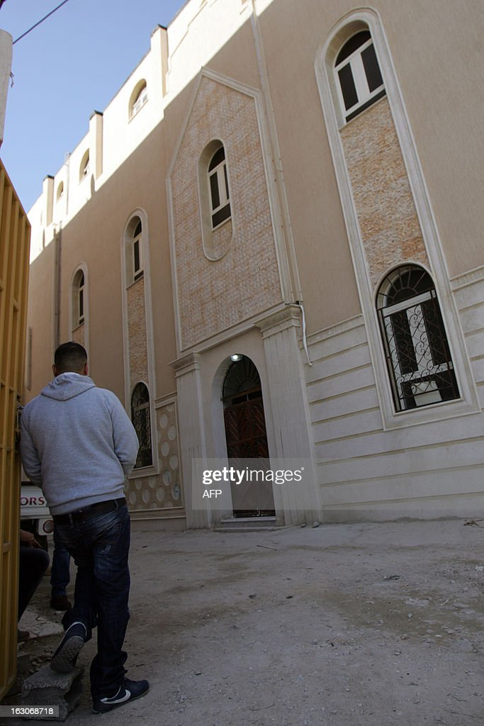 A man leans on a gate close to the Egyptian Coptic church that was attacked the previous night on March 4, 2013 in the eastern city of Benghazi. Gunmen attacked the Egyptian Coptic church in Libya's eastern city, assaulting two priests, the foreign ministry said on March 3, days after dozens of Egyptian Christians suspected of proselytising were arrested.