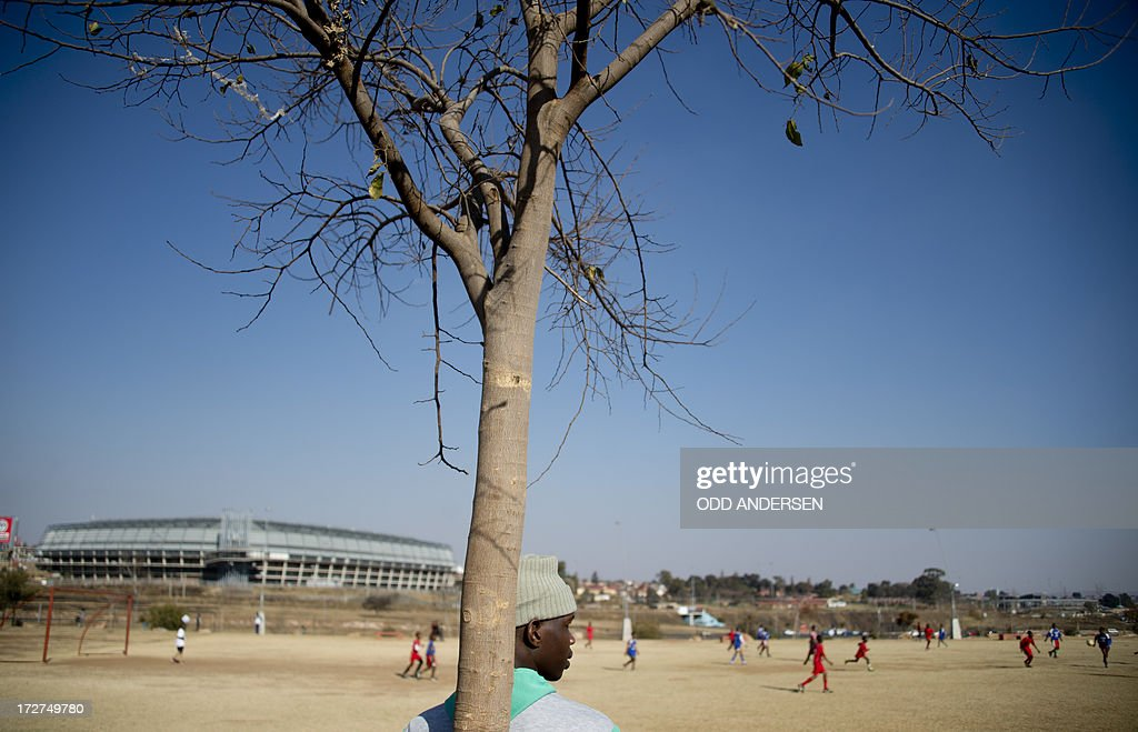 A man leans on a tree while watching a football match between Liverpool and Siyanqoba, in Orlando West park in Soweto on July 4, 2013. South African schools are out for their winter break which has seen an increase in young well-wishers leaving get well messages at various locations for former South African President Nelson Mandela who remains in a Pretoria hospital with a lung infection.