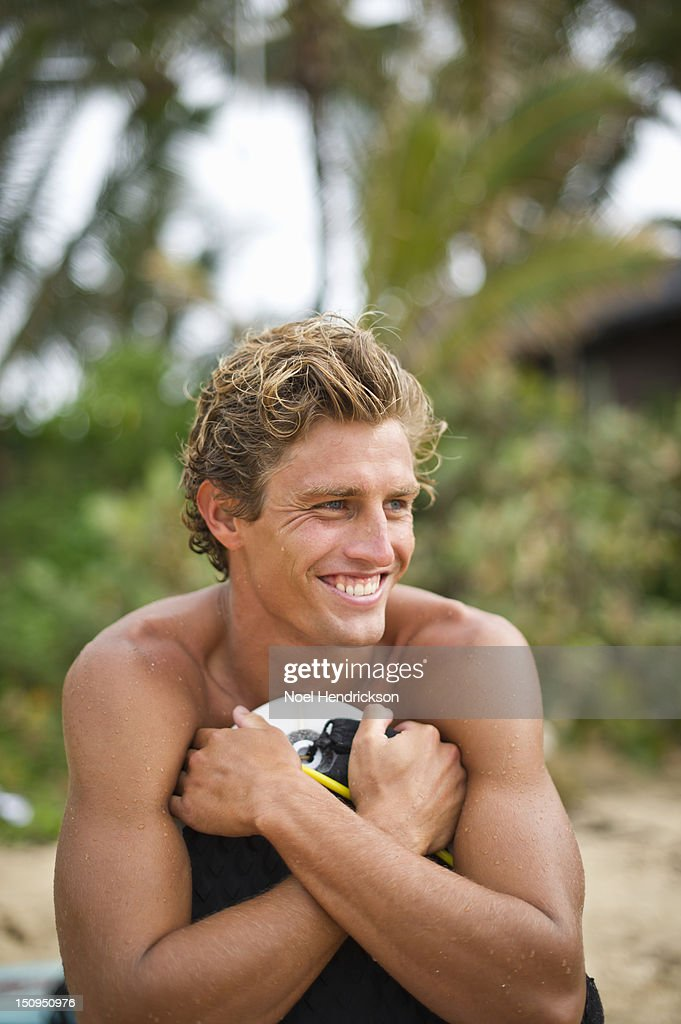 A man leans on his boogie board at the beach : Stock Photo