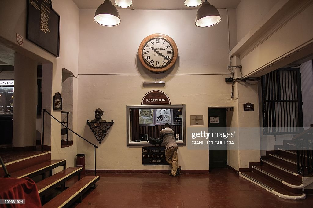 A man leans on the reception counter inside the Historic Market Theatre in Johannesburg on February 10, 2016. In 2016 the iconic Market Theatre marks its 40th anniversary, and as part of the celebrations some of its most socially relevant production will be revived to entertain and challenge a new audience. The Market Theatre was founded by theatre thespians Mannie Manim and Simon Barney, who were disturbed by the absence of a theatre that represented the voice of the majority or reflected what was happening in the skewed society of that era. / AFP / GIANLUIGI GUERCIA