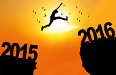 Silhouette of young man jumping over a cliff with numbers 2015 and 2016 at sunset time