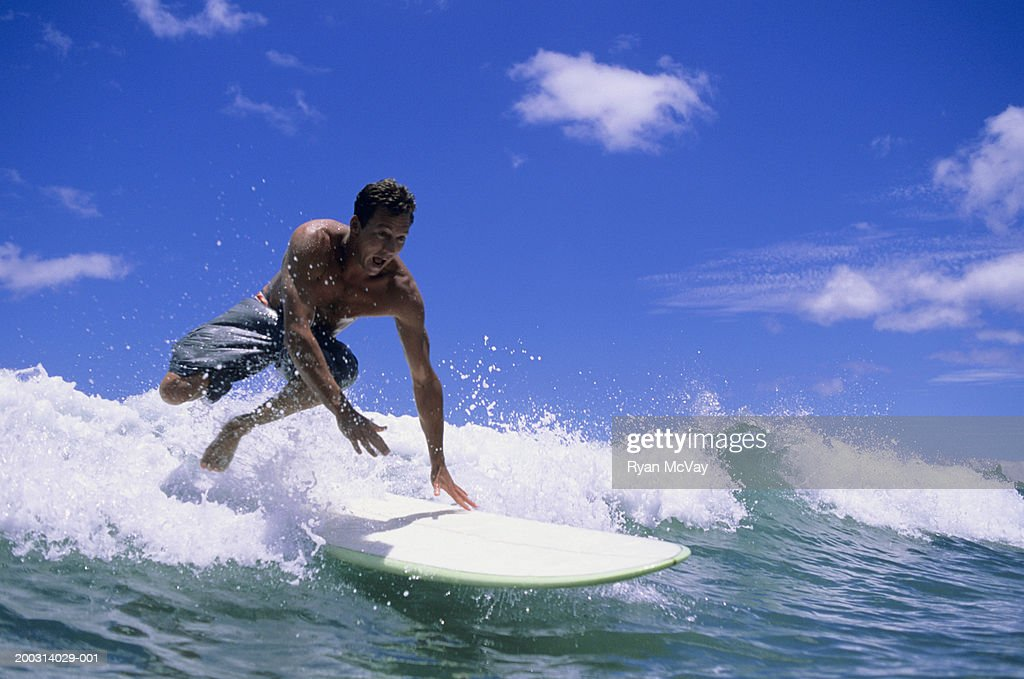 Man leaping from of surfboard in sea : Stock Photo