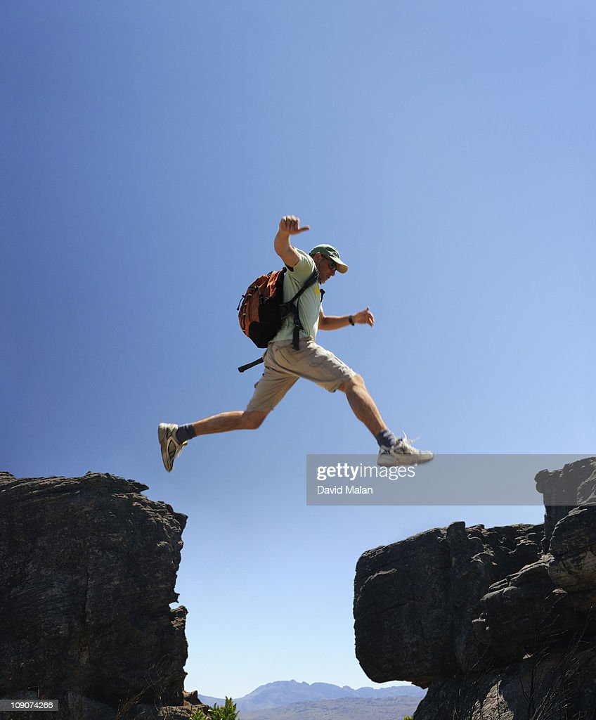 Man leaping from one rock to another. : Stock Photo