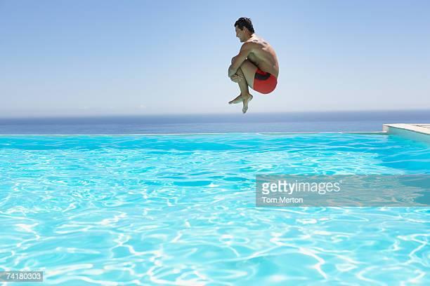 Homme volant dans la piscine à débordement