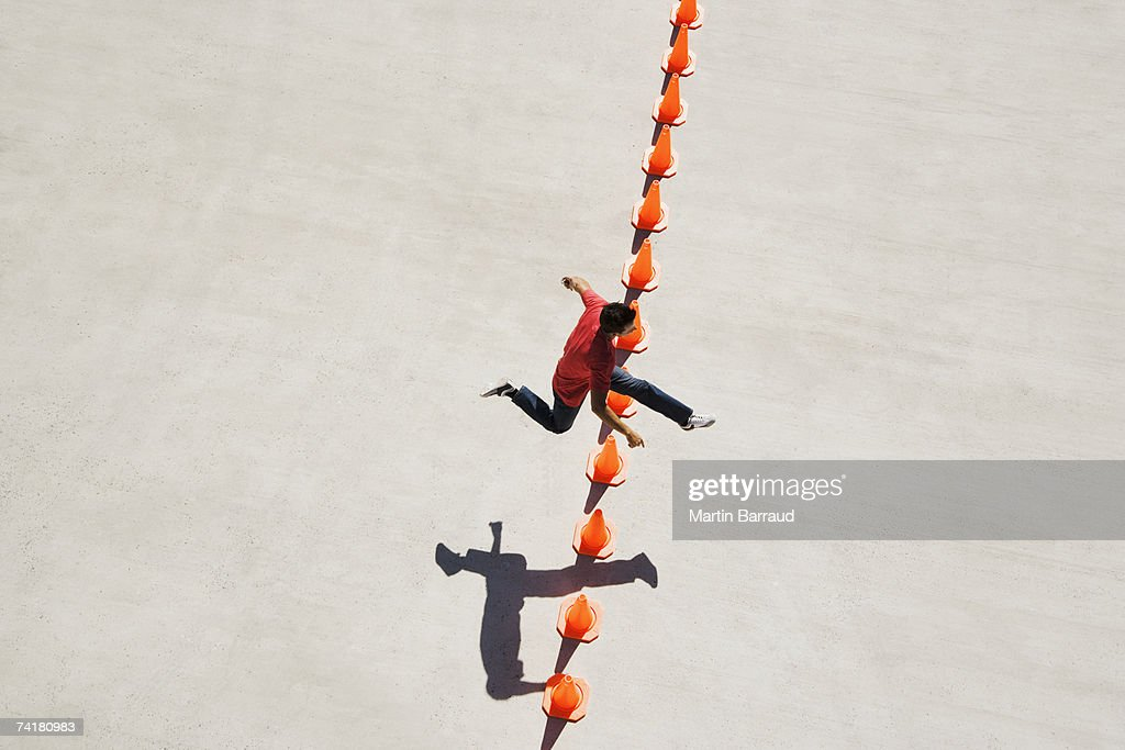 Man leaping over row of traffic cones : Stock Photo