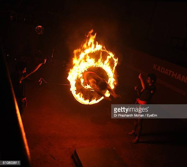 Man leaping through burning rings of fire at night