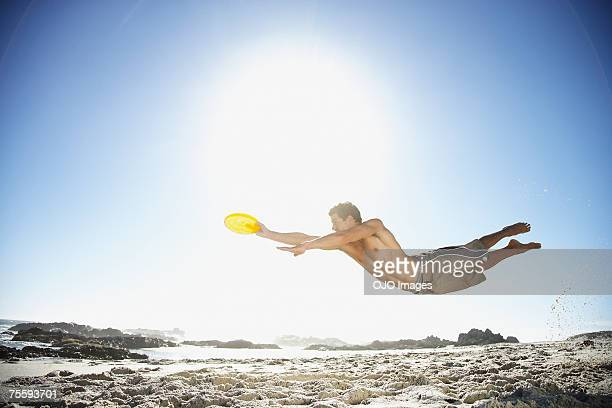 A man leaping through the air at the beach catching a Frisbee