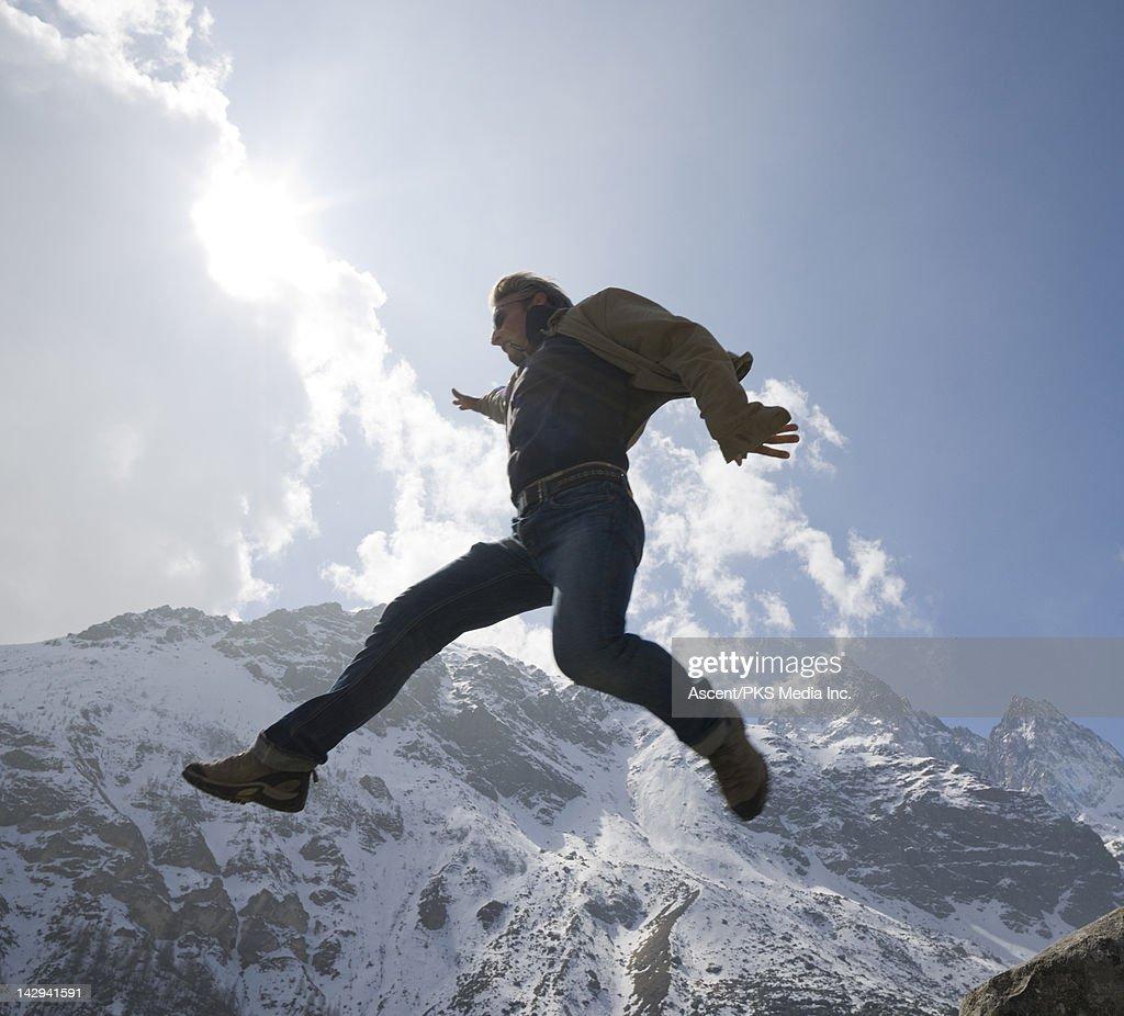 Man leaps between rocks, mountain ridge