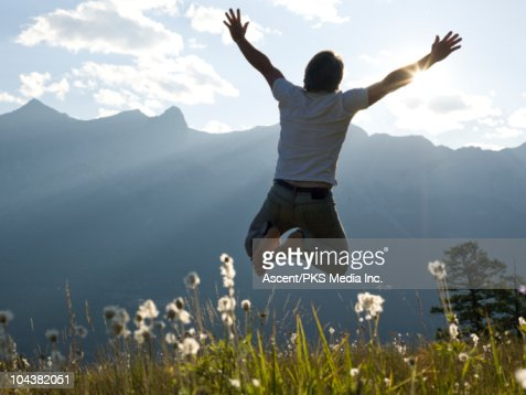 Man leaps for joy in mountain meadow, sunset : Stock Photo
