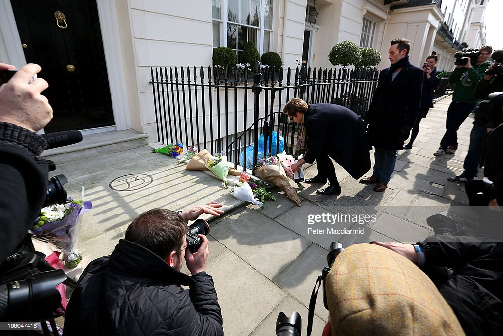 A man leaves a book next to floral tributes outside the residence of Baroness Thatcher in Chester Square in front of photographers and members of the media on April 8, 2013 in London, England. It has been confirmed that Lady Thatcher has died this morning following a stroke aged 87. Margaret Thatcher was the first female British Prime Minster and governed the UK from 1979 to 1990. She led the UK through some turbulent years and contentious issues including the Falklands War, the miner's strike and the Poll Tax riots.