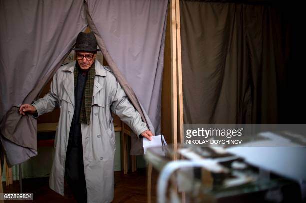 A man leaves a voting booth before casting his ballot at a polling station in Sofia on March 26 during the country's parliamentary election...