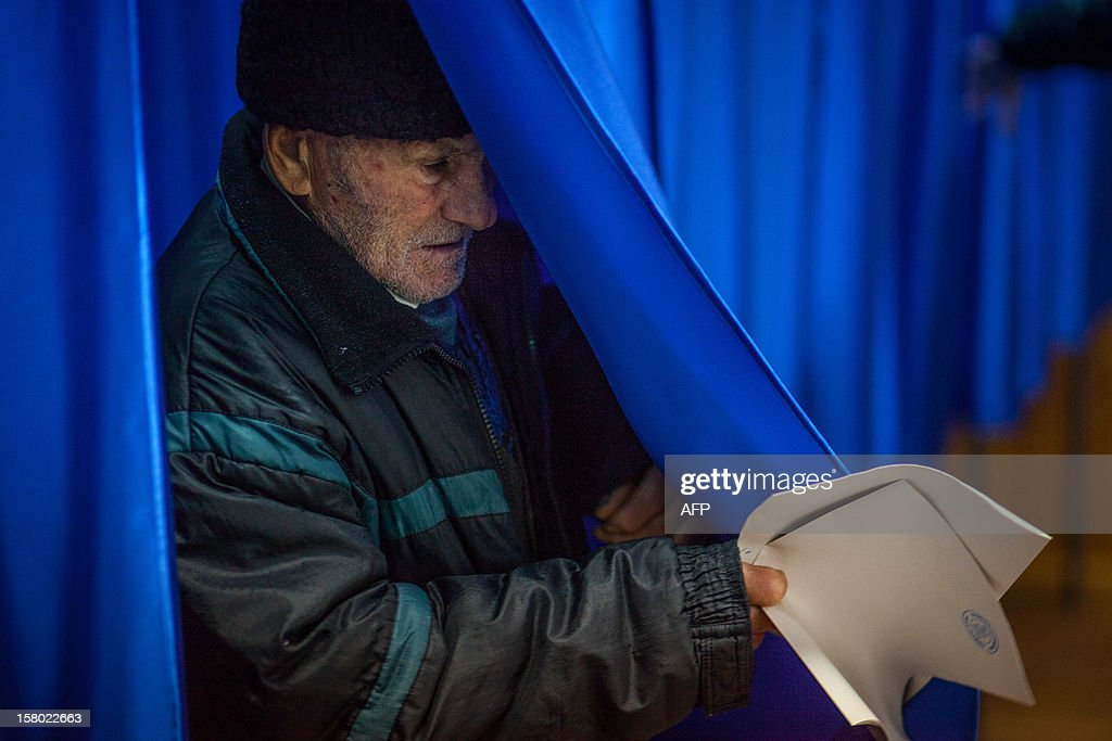 A man leaves a voting cabin with his ballot at a polling station in Bucharest, Romania on December 9, 2012. Austerity-weary Romanians voted for a new parliament Sunday, with the centre-left ruling coalition on course for a large victory that was likely to trigger fresh tension between the party and rival president Traian Basescu.
