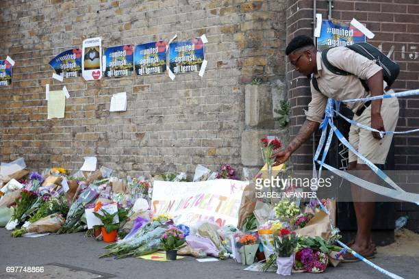 A man leaves flowers beside the police cordon close to the scene of a van attack in Finsbury Park north London on June 19 2017 Ten people were...