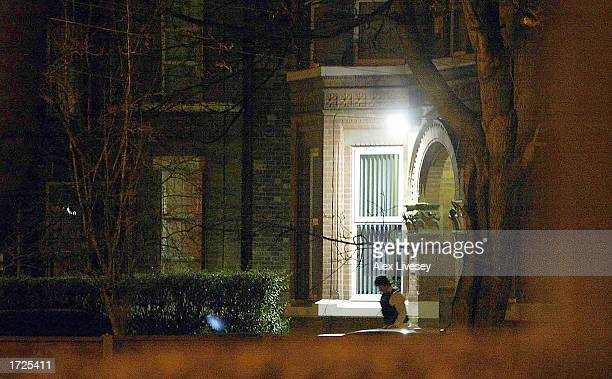 A man leaves the apartment where a police officer was stabbed to death during the arrest of three terror suspects in a raid January 14 2003 in...