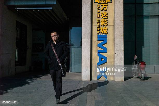 A man leaves the Wanda cinema next to the Wanda Group building in Beijing on January 12 2016 Chinese conglomerate Wanda Group is buying US film...