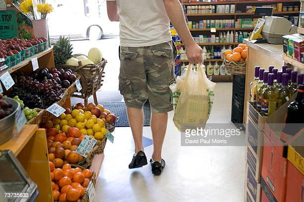 A man leaves with a bag of groceries in a plastic bag made of recyclable material at the Nature Shop on March 28 2007 in San Francisco California The...