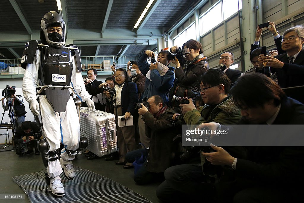 A man, left, demonstrates the Hybrid Assistive Limb (HAL) work-assist robot suit, developed by Cyberdyne Inc. in the New Energy and Industrial Technology Development Organization's (NEDO) unmanned anti-disaster system research and development project, during a media review at Chiba Institute of Technology's (CIT) Shibazono campus in Narashino City, Chiba Prefecture, Japan, on Wednesday, Feb. 20, 2013. NEDO, Japan's largest public R&D management organization, introduced its latest disaster response robot technologies today. Photographer: Kiyoshi Ota/Bloomberg via Getty Images