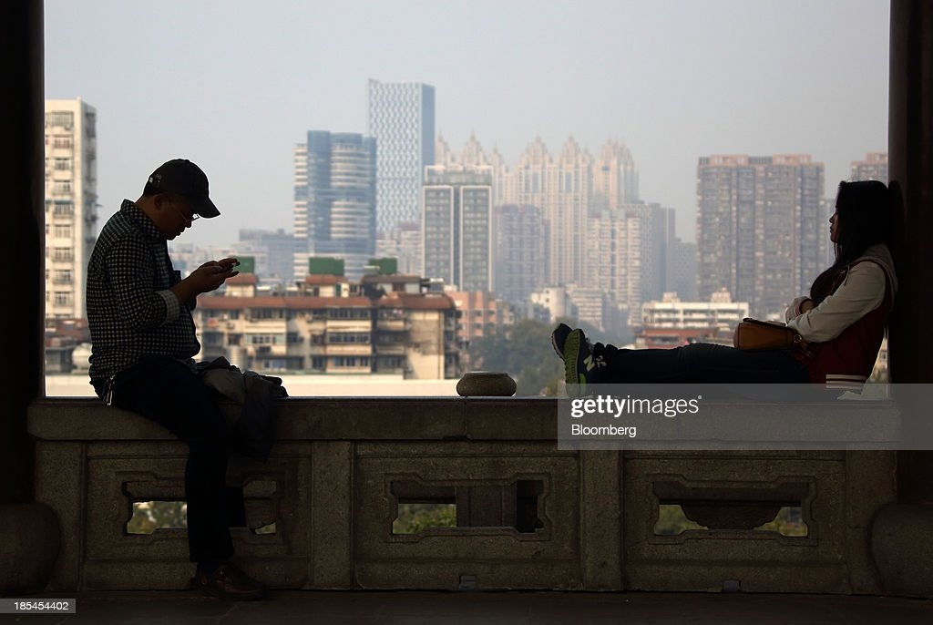 A man, left, uses a smartphone while a woman sits at the Yellow Crane Tower in Wuhan, China, on Sunday, Oct. 20, 2013. China's economic expansion accelerated to 7.8 percent in the third quarter from a year earlier, the statistics bureau said Oct. 18, reversing a slowdown that put the government at risk of missing its 7.5 percent growth target for 2013. Photographer: Tomohiro Ohsumi/Bloomberg via Getty Images