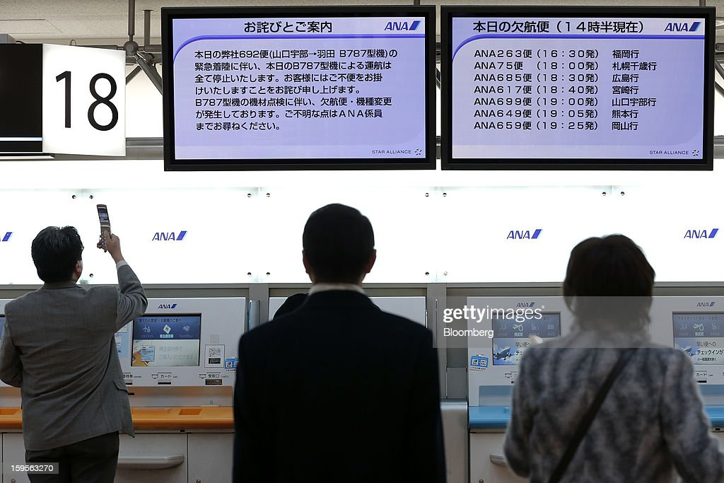 A man, left, uses his mobile phone to take a photograph of an electronic board displaying information on canceled All Nippon Airways Co. (ANA) flights at Haneda Airport in Tokyo, Japan, on Wednesday, Jan. 16, 2013. ANA and Japan Airlines Co. (JAL), the world's largest users of Boeing Co. 787 jets, grounded their entire fleet of Dreamliners for today in the biggest blow yet to the troubled passenger jet's image. Photographer: Kiyoshi Ota/Bloomberg via Getty Images