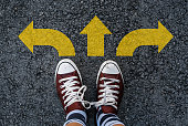 man legs in sneakers standing on road with three direction arrow choices, left, right or move forward