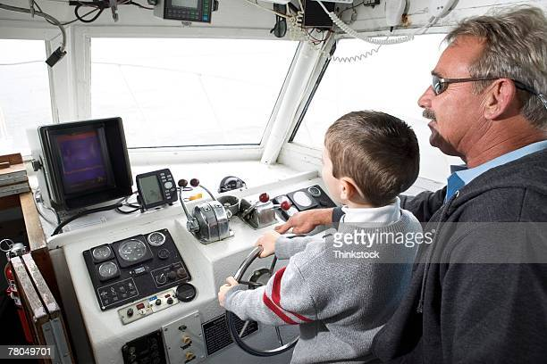 Man letting boy steer boat