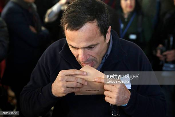 A man licks a ballot envelope at a polling station in Madrid on December 20 2015 Spaniards go to the polls today in what is expected to be one of the...