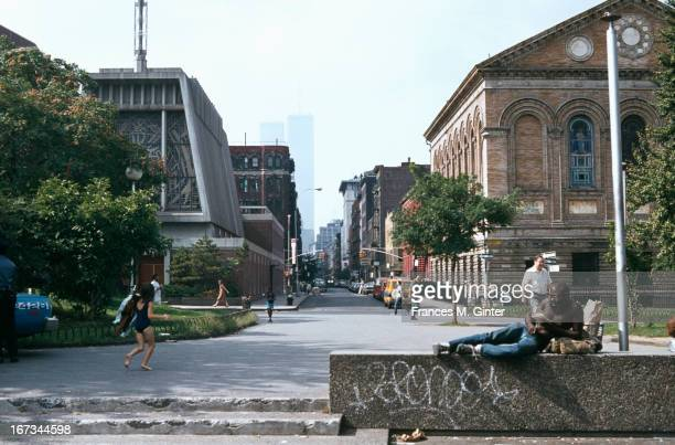 A man lies across a ledge on the south side of Washington Square Park with New York University and the Twin Towers behind August 1979