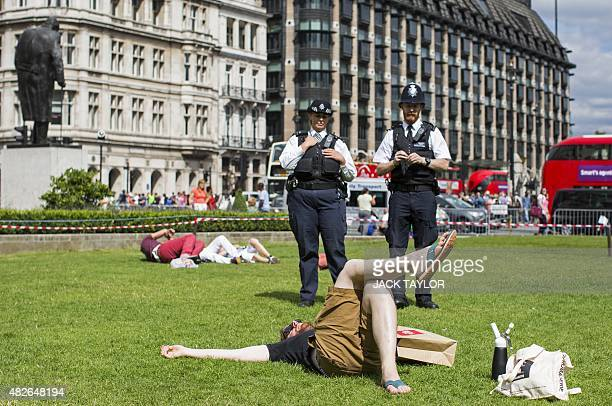 A man lies down on the grass in front of two police officers following a mass inhalation of Nitrous Oxide commonly known as laughing gas outside the...