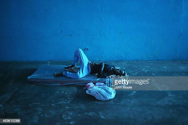 A man lies in a newlyopened Ebola isolation center set up by the Liberian health ministry in a closed school on August 14 2014 in Monrovia Liberia...