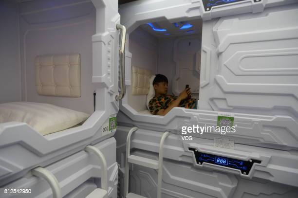 A man lies in a 'sleepsharing' capsule at a hotel in Zhongguancun on July 11 2017 in Beijing China Customers can rent the sleepsharing capsules by...