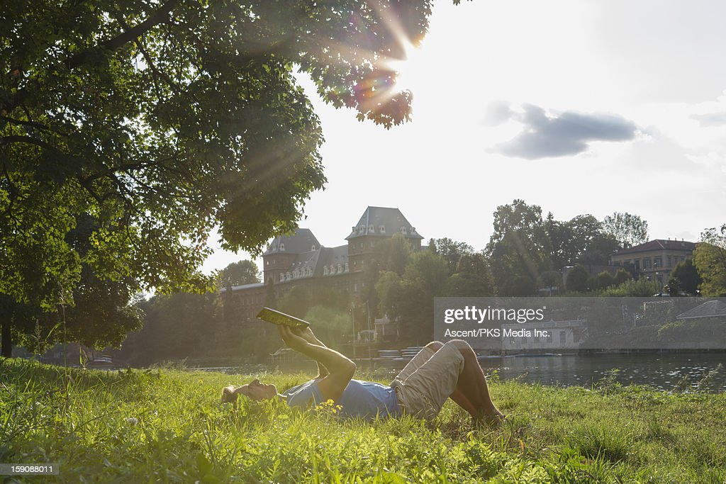 Man lies in grass, uses digital tablet, urban park : Stock Photo