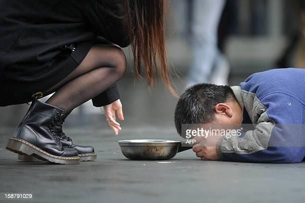 A man lies on a footbridge to beg for money as pedestrians walk past in Hong Kong on December 29 2012 Hong Kong plans to raise the city's minimum...