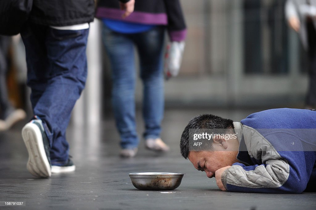 A man lies on a footbridge to beg for money as pedestrians walk past in Hong Kong on December 29, 2012. Hong Kong plans to raise the city's minimum wage to 30 HKD (3.87 USD) an hour, a minister said on December 12, in a hike slammed by labour groups as inadequate for the Asian financial hub. Known for its stunningly wealthy tycoons, the southern Chinese city is also home to hundreds of thousands of workers who live on hourly wages sometimes as low as 2 USD an hour prior to the introduction of the minimum wage. AFP PHOTO / ANTHONY WALLACE