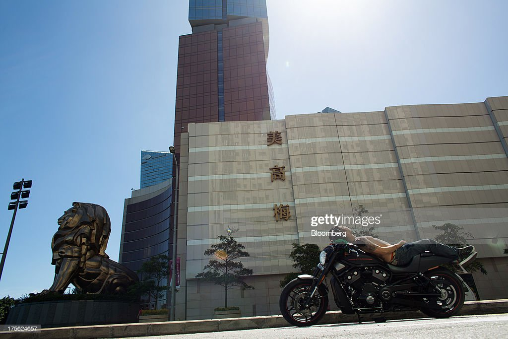 A man lies on a motorbike outside the MGM Macau, operated by MGM China Holdings Ltd., in Macau, China, on Sunday, Aug. 4, 2013. MGM China Holdings is scheduled to release second quarter results on Aug. 6. Photographer: Lam Yik Fei/Bloomberg via Getty Images