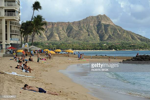 A man lies on the beach in front of a line of concrete security barriers placed on Waikiki Beach November 9 2011 in Honolulu Hawaii as part of...