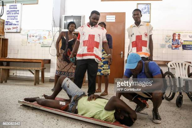 A man lies on the floor as he awaits treatment by medical staff at the Secondary Hospital at Be Lome on October 19 after he was shot and wounded in...
