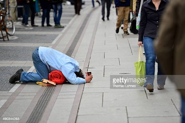 A man lies on the ground and begs for money on May 6 2014 in Frankfurt am Main Germany Numerous beggars ask in Frankfurt's Zeil shopping street...