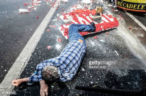 A man lies on the ground near a destroyed sign made with red and white carnations and a banner reading 'Struggle' after Turkish police used a water...