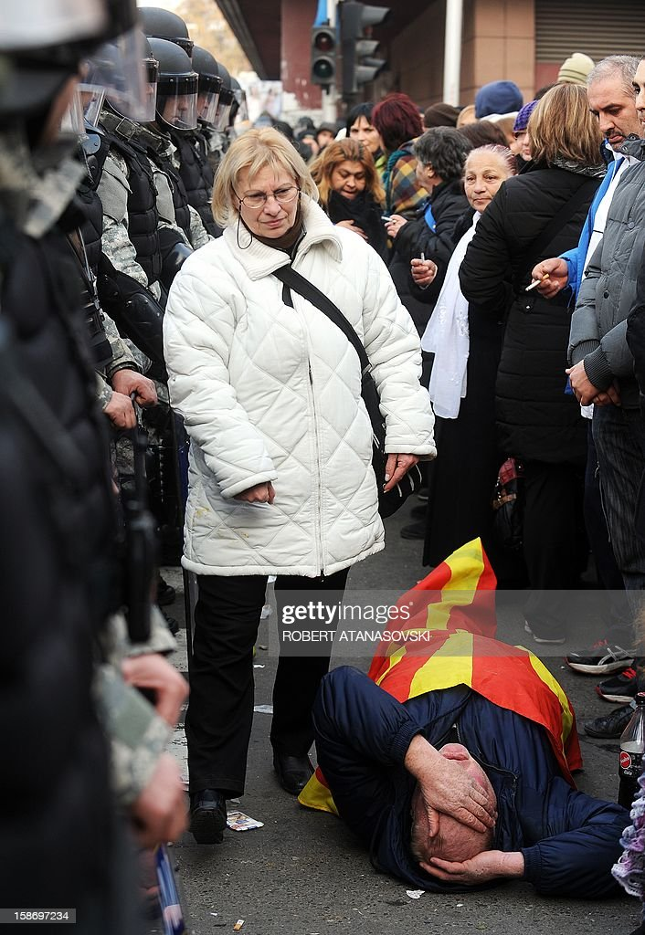 A man lies on the ground wrapped in a Macedonian flag as pupporters of members of the Macedonian Assembly from the opposition SDSM (Social Democratic Union of Macedonia) party, who attempted to blocade a session of parliament dedicated to a vote on the 2012 budget, protest outside the Macedonian parliament in Skopje on December 24, 2012, against the passing of the 2013 budget. Although leftist deputies from the Macedonian opposition party SDSM barricaded themselves in parliament to try to prevent adoption of a 2013 budget that they say will lead to excessive public debt, the ruling party adopted the 2013 budget with 64 MPs voting in favor.