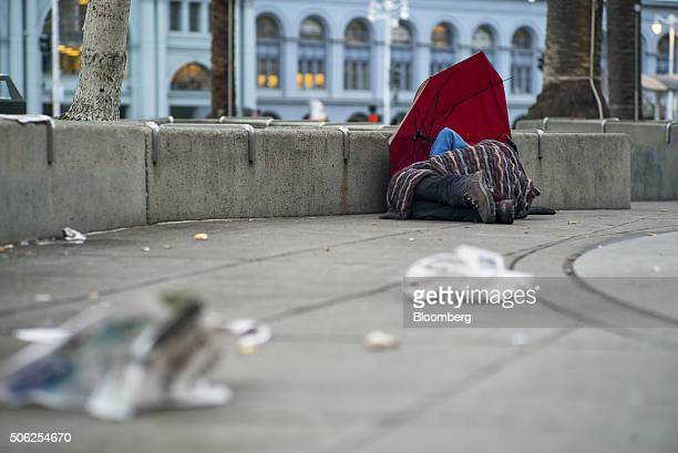 A man lies under a blanket by an umbrella in Justin Herman Plaza in San Francisco California US on Thursday Jan 21 2016 San Francisco host city for...