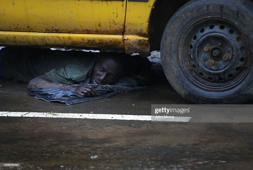 A man lies under a car after being put there in detention by the Liberian army on the second day of the government's Ebola quarantine on their neighborhood of West Point on August 21, 2014 in Monrovia, Liberia. An army officer said that he was showing symptoms of Ebola and was caught trying to escape from West Point. The government delivered bags of rice, beans and cooking oil to residents, who are forbidden from leaving the seaside slum, due to the Ebola outbreak in their community. More than 1,200 people have died due to the Ebola epidemic in West Africa.