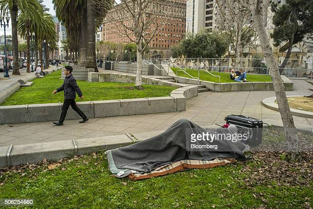A man lies underneath a blanket next to a suitcase in front of Justin Herman Plaza in San Francisco California US on Thursday Jan 21 2016 San...