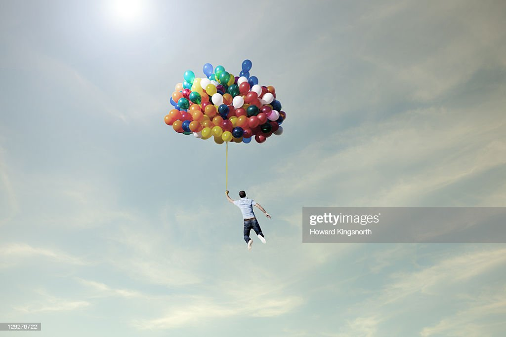 man lifted into sky by huge bunch of balloons : Stock Photo