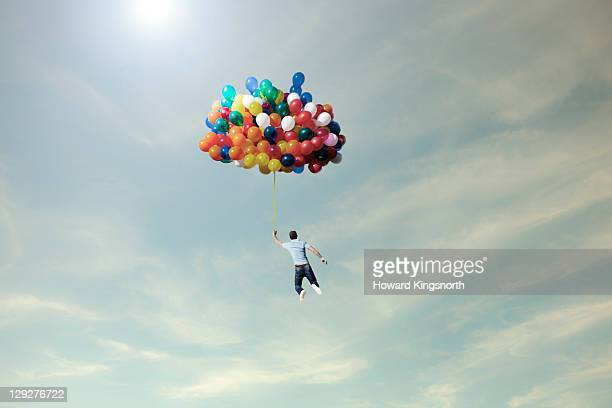 man lifted into sky by huge bunch of balloons