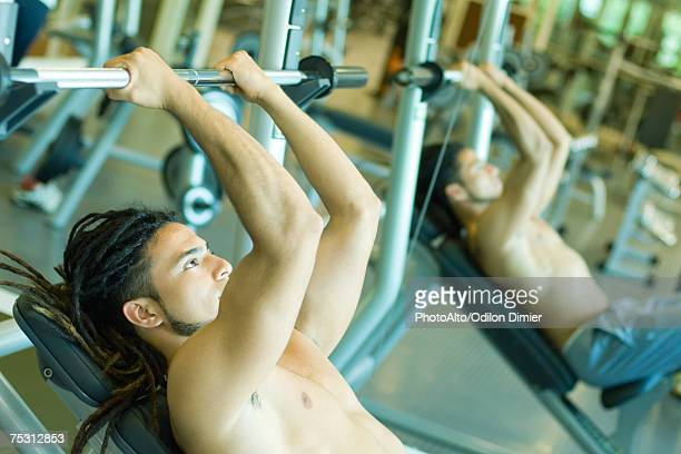 Man lifting barbell, reflected in mirror