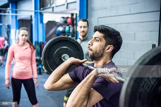 Man lifting barbell weights in gym