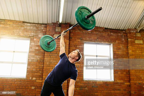 Man lifting barbell with one hand